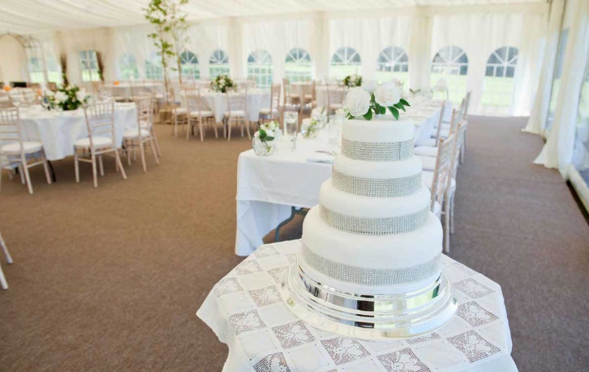 Wedding marquee with tables set up for dining and the 4 tier white wedding cake on the corner table beside the top table