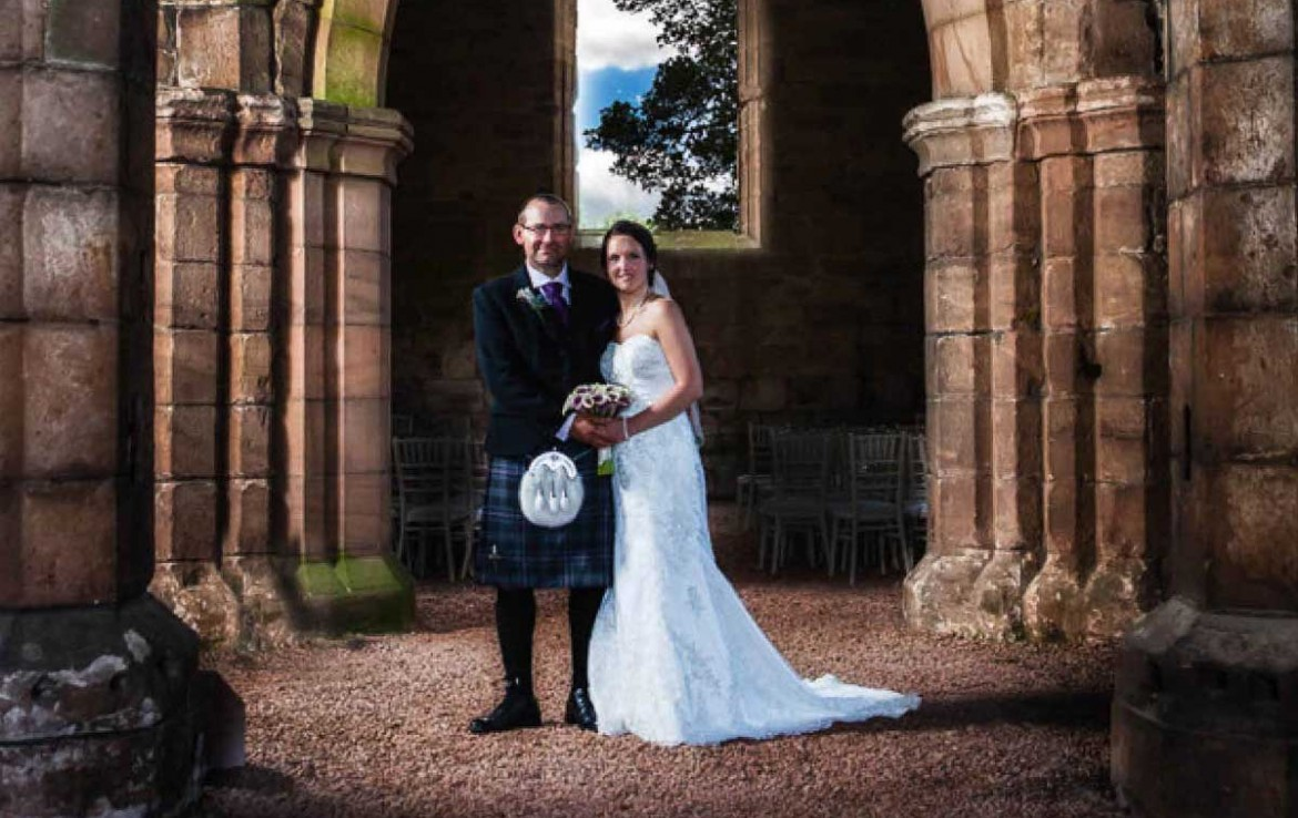 Bride and Groom standing outside Dunglass Estate Church entrance