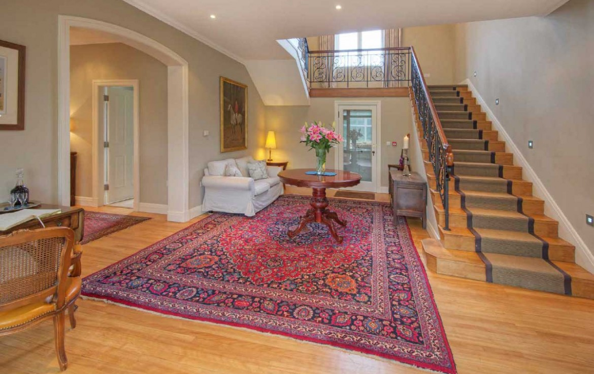 Hall of Dunglass Estate House with persian carpet, oak staircase turning to left and comfortable couch under stairs