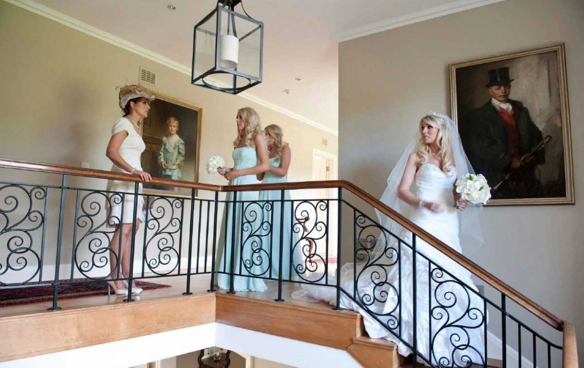Wedding party in Dunglass Estate with bride descending stairs and bridesmaids behind