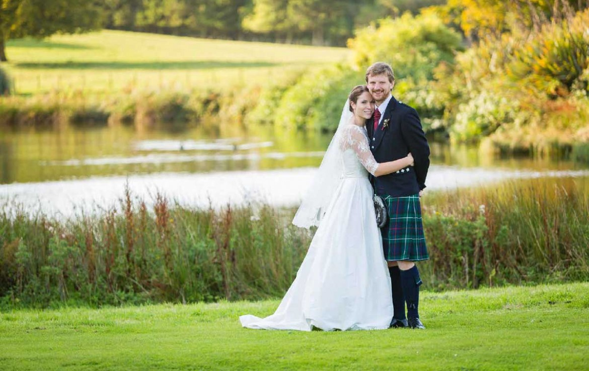 Wedding couple on the banks of the river at Dunglass Country House Estate